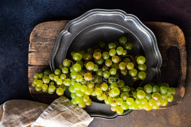 Overhead view of a green grapes on a vintage pewter plate — Stock Photo