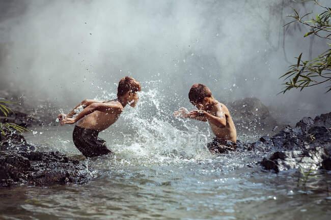 Dos chicos lavándose en un río, Tailandia - foto de stock