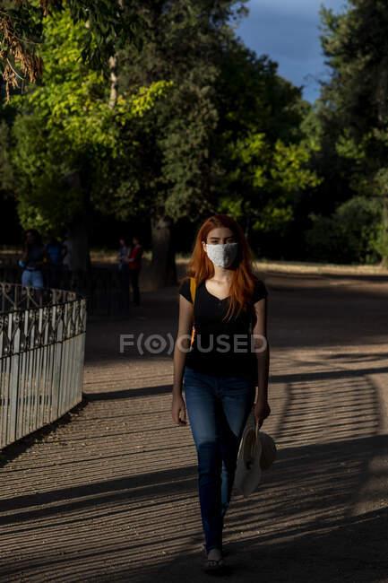 Жінка в масці на обличчі ходить на віллі Боргезе, Рим, Лаціо, Італія. — стокове фото