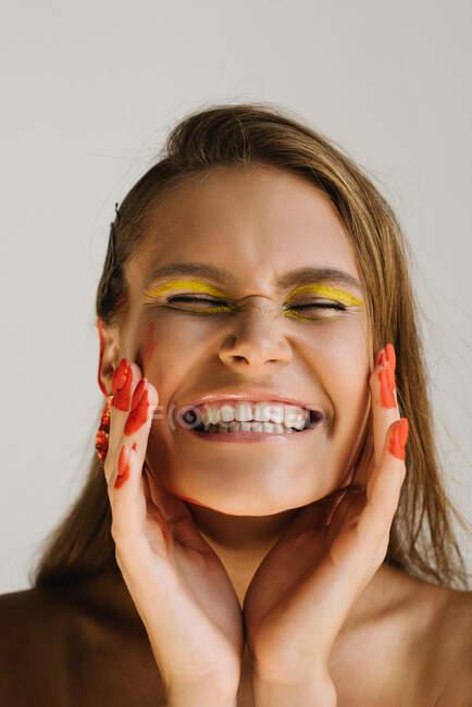 Портрет улыбающейся женщины с необычным макияжем — стоковое фото
