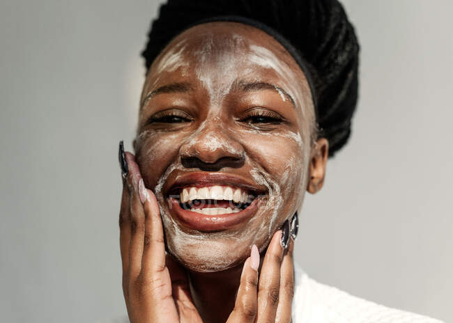 Retrato de uma mulher sorridente com uma máscara facial — Fotografia de Stock