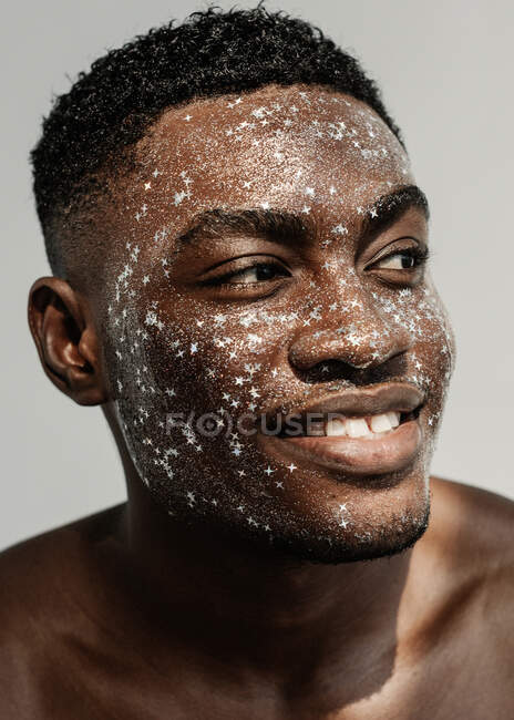 Портрет улыбающегося мужчины с блестками на лице — стоковое фото