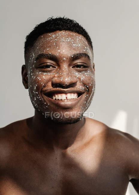 Retrato de un hombre sonriente con purpurina en la cara - foto de stock