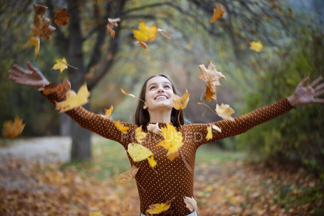 Portrait of a smiling girl throwing autumn leaves in the air, Bulgaria — Stock Photo