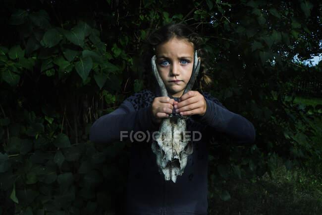 Retrato de una niña al aire libre sosteniendo un cráneo de animal, Polonia - foto de stock