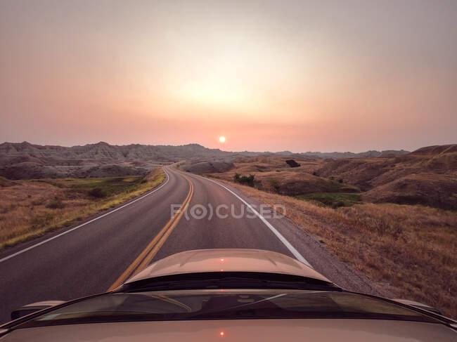 Coche conduciendo a lo largo de la carretera al atardecer durante incendios forestales, Parque Nacional Badlands, Dakota del Sur, EE.UU. - foto de stock