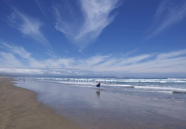 Quatro pessoas, caminhando ao longo de Ninety Mile Beach, North Island, Nova Zelândia — Fotografia de Stock