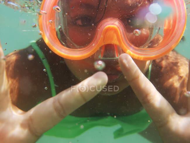 Close-up de uma menina debaixo d 'água usando uma máscara de mergulho, Itália — Fotografia de Stock