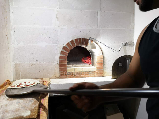 Man about to cook a pizza in a pizza oven — Stock Photo