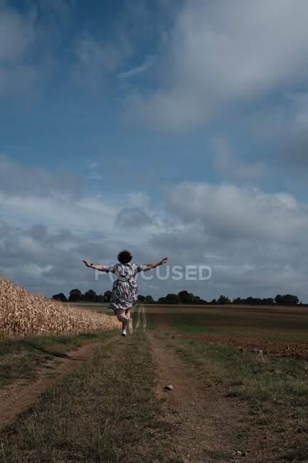 Veduta posteriore di una donna che cammina lungo un sentiero di campagna saltando in aria, Francia — Foto stock