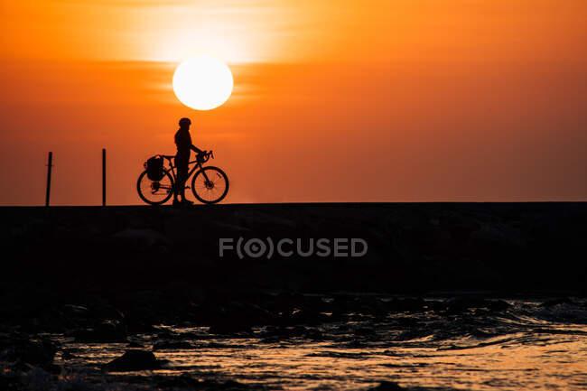 Silueta de un ciclista de pie frente al mar al amanecer, Fuengirola, Málaga, España - foto de stock