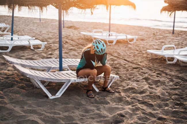 Ciclista estresada en la playa con la cabeza en las manos, Fuengirola, Málaga, España - foto de stock