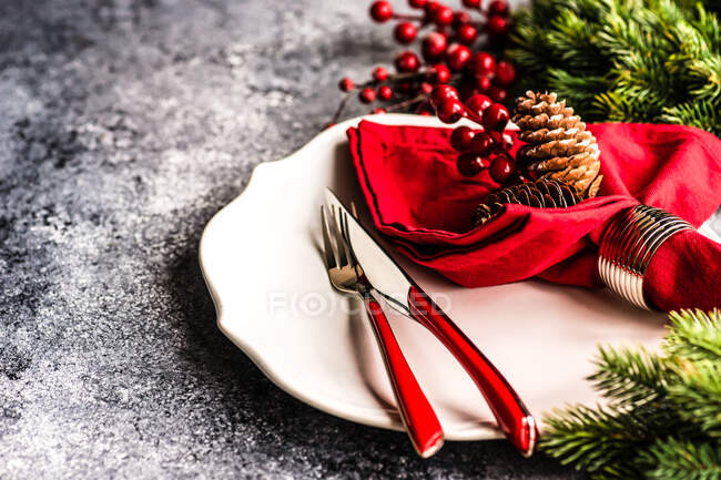 Table setting on stone background with ceramic white plate and red decorated napkin and cutlery for holiday Christmas dinner — Stock Photo