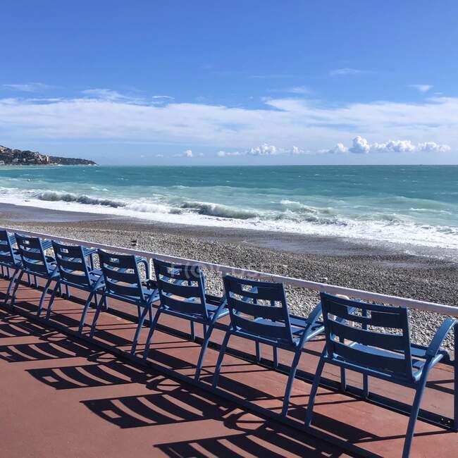 Fila di sedie in metallo in riva al mare sulla Promenade des Anglais, Nizza, Alpes-Maritimes, Francia — Foto stock