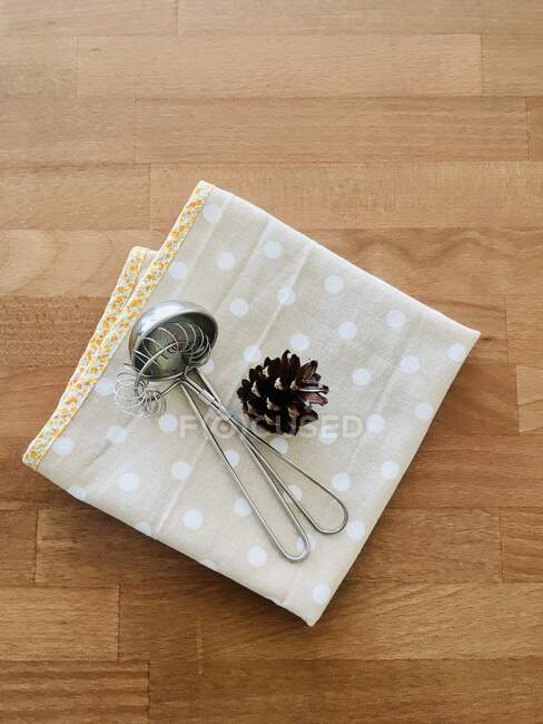 Overhead view of cooking utensils and a pinecone on a folded tea towel — Stock Photo