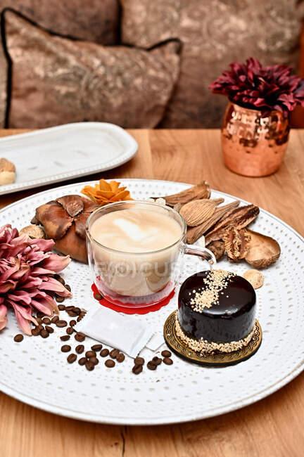 Bolo de chocolate e xícara de café em um prato com decorações rústicas — Fotografia de Stock