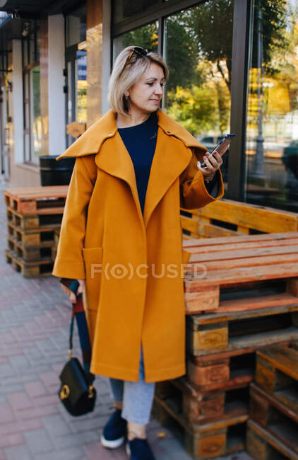 Smiling woman standing in the street looking at her mobile phone, Russia - foto de stock