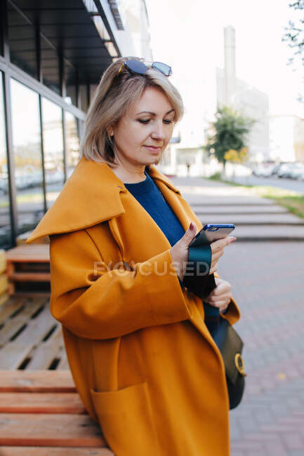 Portrait of a mature woman standing in the street looking at her mobile phone, Russia - foto de stock