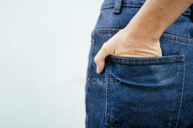 Primer plano de la mano húmeda de una mujer en el bolsillo de su vaquero - foto de stock