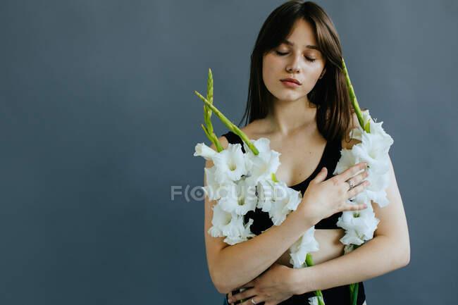 Retrato de una hermosa mujer sosteniendo flores de gladiolos blancos - foto de stock