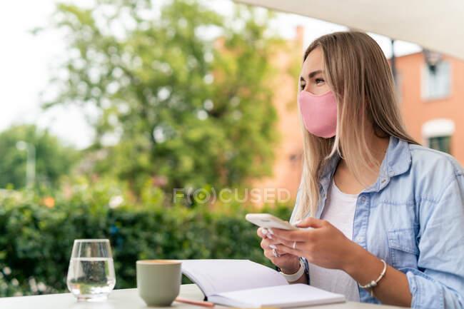 Mulher usando uma máscara facial usando seu telefone celular — Fotografia de Stock