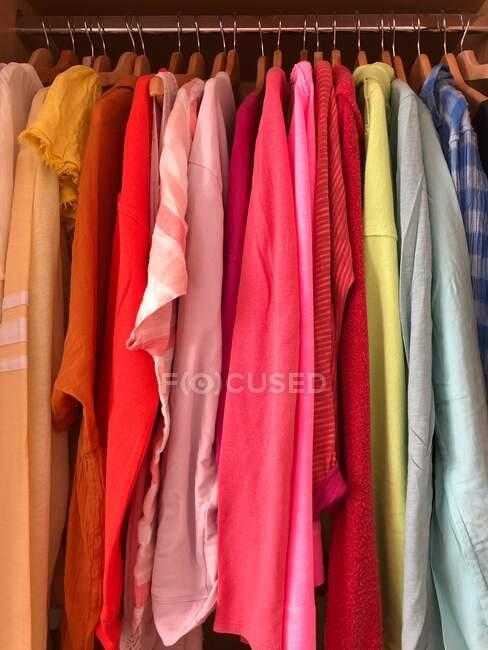 Tops coloridos arco-íris pendurados em um guarda-roupa — Fotografia de Stock