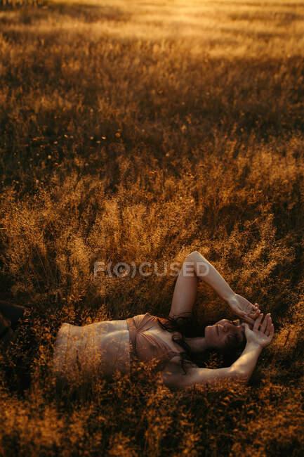 Жінка лежала на полі влітку на заході сонця (Росія). — стокове фото