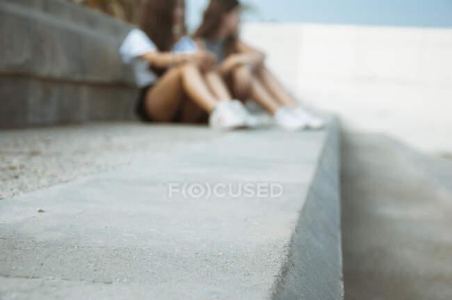 Мать и дочь сидят на ступеньках в ожидании, Испания — стоковое фото
