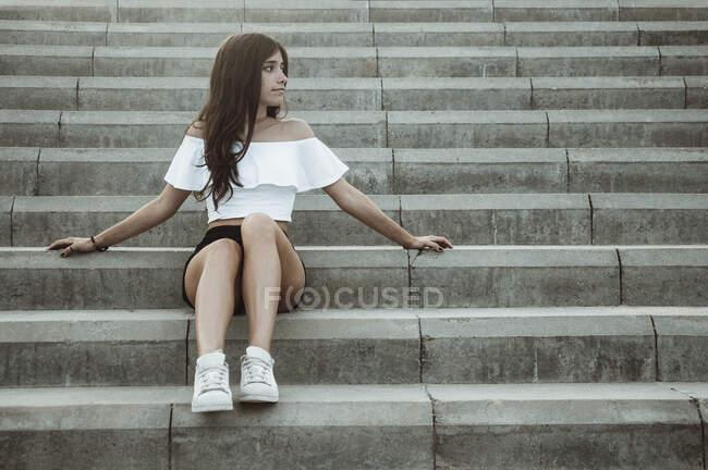 Девочка-подросток сидящая на ступеньках, Испания — стоковое фото