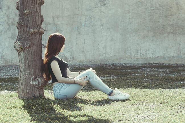 Девочка-подросток сидит в саду, прислонившись к дереву, Испания — стоковое фото