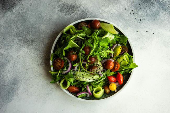 Свіжий овочевий салат з насінням кунжуту подають у мисці. — стокове фото