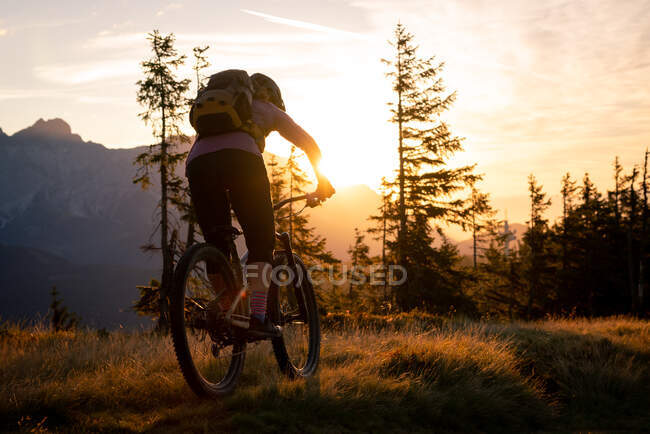 Rear view of a woman mountain biking in mountains at sunrise, Fadstadt, Salzburg, Austria — Stock Photo