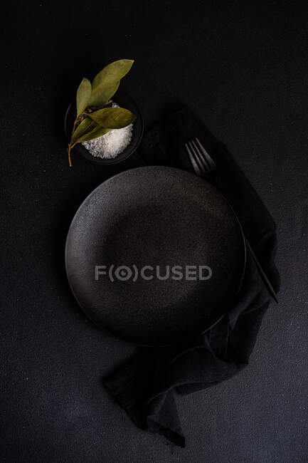 Overhead view of dish filled with rock salt and bay leaves next to a plate — Stock Photo