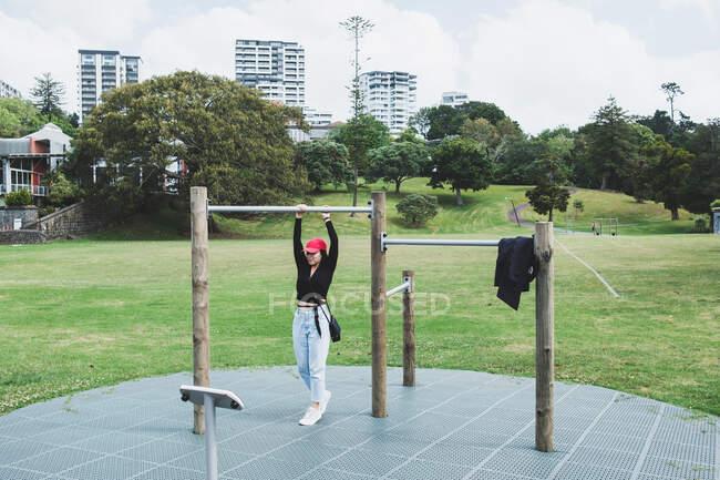 Mujer haciendo ejercicio en un bar de actividades en el parque, Auckland, Isla Norte, Nueva Zelanda - foto de stock