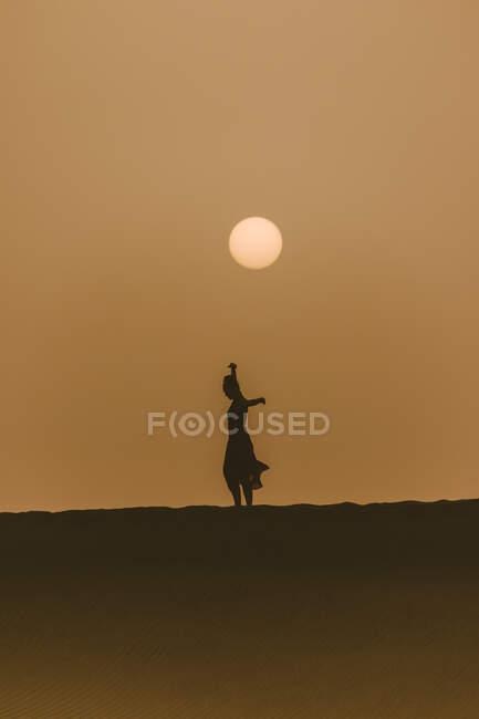Silueta de mujer bailando en la playa al atardecer, Dunas de Maspalomas, Las Palmas, Gran Canaria, Islas Canarias, España - foto de stock