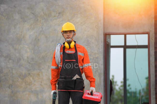 Porträt eines Elektrikers mit seinen Werkzeugen vor einem neu gebauten Haus, Thailand — Stockfoto