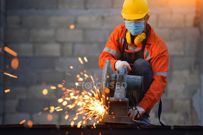Промисловий працівник у масках для нарізання металу металевим шліфувальником. — стокове фото