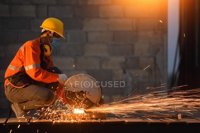 Trabajador industrial que usa una mascarilla facial que corta metal con una amoladora de metal - foto de stock