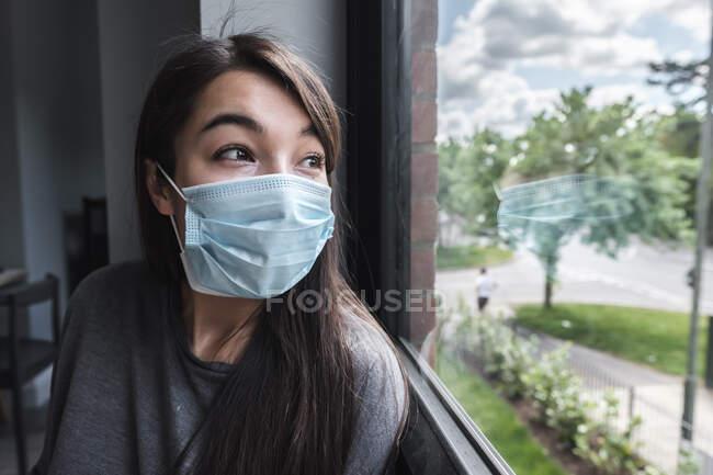 Жінка в масці обличчя дивиться у вікно під час блокування — стокове фото