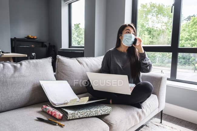 Mulher sentada em um sofá trabalhando em casa durante o confinamento — Fotografia de Stock