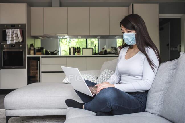 Mulher sentada no sofá usando uma máscara facial trabalhando em casa — Fotografia de Stock