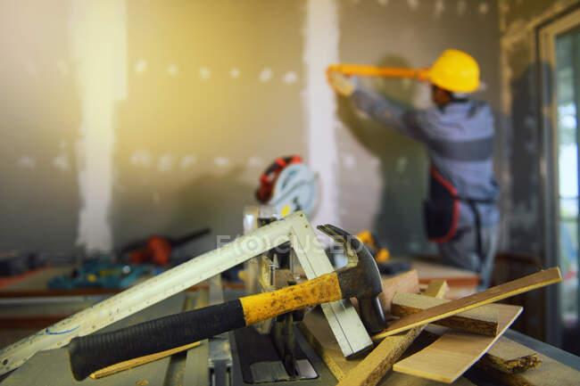 Engenheiro de construção medindo uma parede em um canteiro de obras — Fotografia de Stock