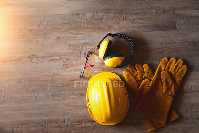 Шолом безпеки, окуляри, рукавички і захисники вуха на дерев'яному столі. — стокове фото