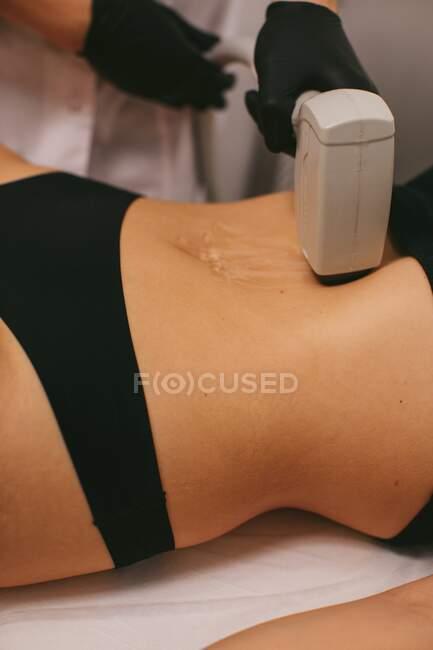Mujer que tiene un tratamiento de depilación láser en un salón de belleza - foto de stock