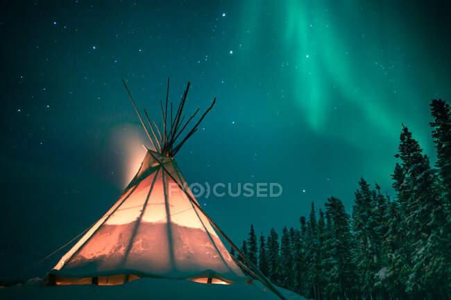 Largo tiro de exposición de tipi brillante en el bosque nevado bajo las luces del norte, Yellowknife, Territorios del Noroeste, Canadá - foto de stock
