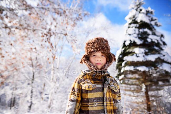 Retrato de um menino usando um boné de caçador na neve, EUA — Fotografia de Stock