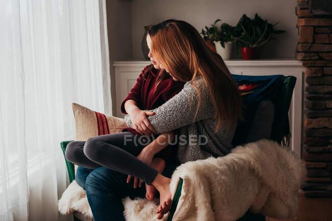 Mãe e filha abraçando em uma poltrona — Fotografia de Stock
