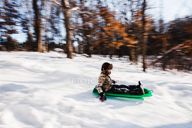 Boy sledding down a hill in the snow, USA — Stock Photo