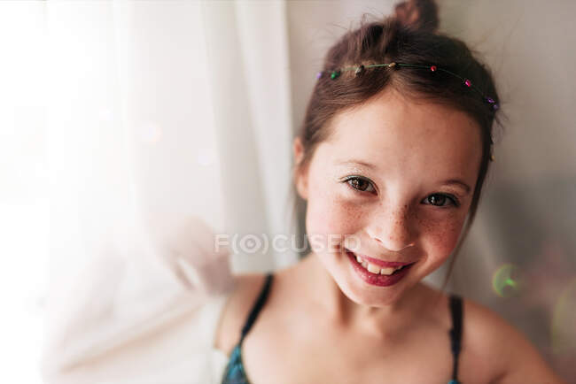 Portrait of a young girl wearing make-up standing by a curtain — Stock Photo