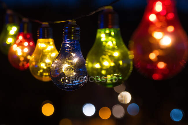 Multi coloured light bulbs hanging in a row at night - foto de stock